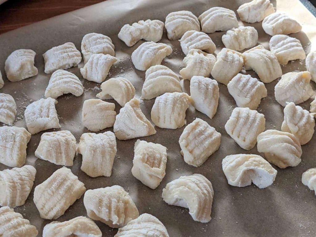 handmade gnocchi lined on a tray waiting to be cooked