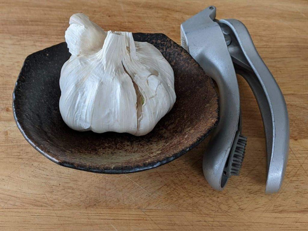 a bulb of garlic and a garlic press on a tabletop