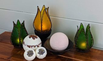 handmade bath bombs with flower petals and candles on a table