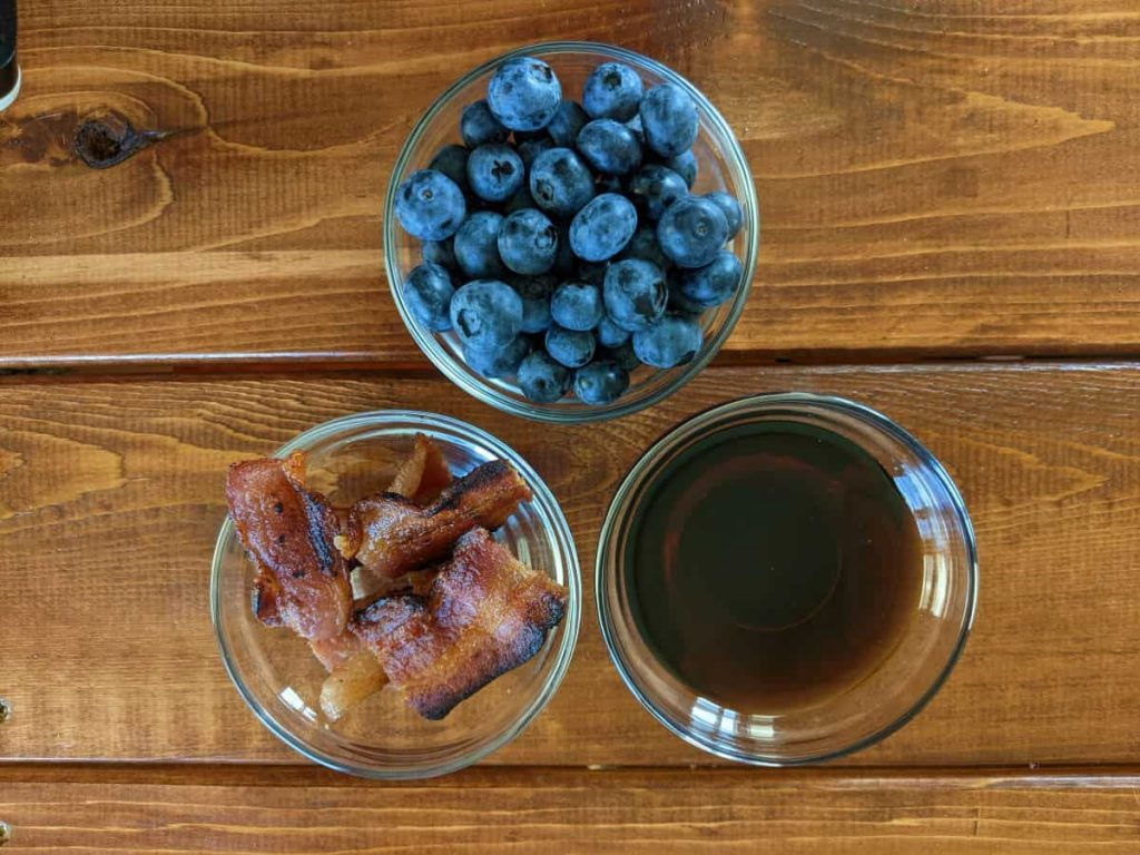 Blueberries, bacon, and syrup in three dishes on a tabletop