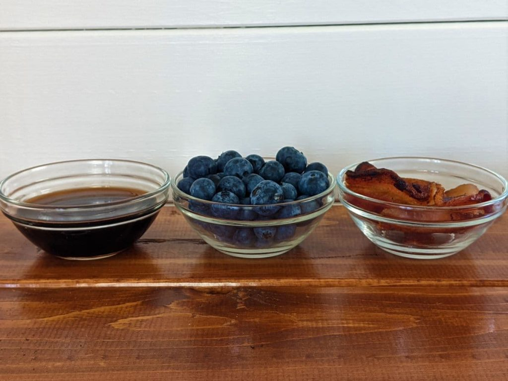 blueberries, bacon, and fresh maple syrup on tabletop to top cupcakes