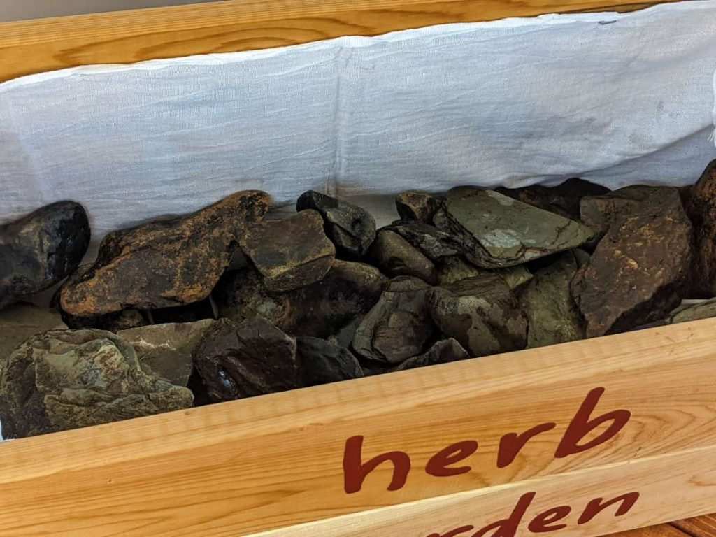 layer of river rocks in a handmade wooden planter