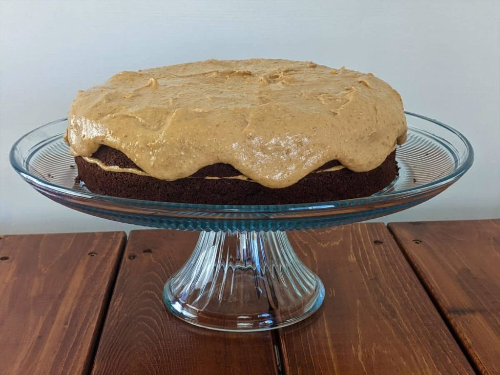 wfpb chocolte peanut butter cake on a cake stand and a table