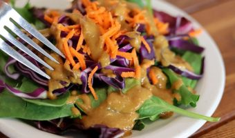 spicy peanut salad dressing on a salad with a fork